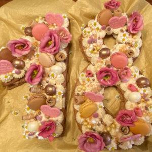 Medové pláty, zdobení krémem z čokolády (bílá, karamelová, mléčná a hořká), makronky, perličky, živé květy.